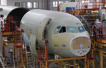 An employee stands next to an A320 plane under construction in Tianjin municipality